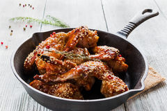 Chicken wings in cast-iron pan on wooden table. Marinated in tomato and honey sauce. Baked with sesame seeds Royalty Free Stock Images