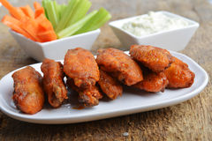 Chicken wings. With celery and carrot on wooden background Stock Photos
