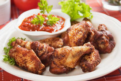 Chicken wings with chili sauce. Chicken wings with lettuce and chili sauce Royalty Free Stock Photography
