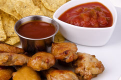 Chicken wings. Closeup of barbecued chicken wings with nachos and salsa Royalty Free Stock Image