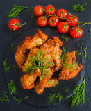 Chicken wings cooked with barbecue sauce on black stone background. Small cherry tomatoes and dill. Top view Stock Images