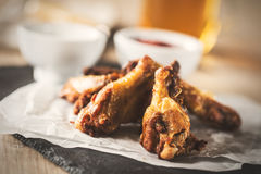 Chicken wings. Delicious crispy chicken wings with sauce and beer. Vintage food edition Royalty Free Stock Image