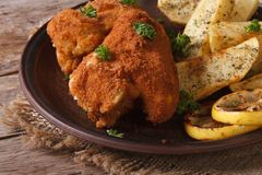 Chicken wings dipped in batter with potatoes and lemon Royalty Free Stock Photo