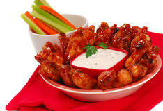 Chicken wings and dipping sauce. Hot and spicy chicken wings with blue cheese dipping sauce along with carrot and celery sticks stock photos