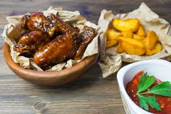Chicken wings in a fragrant and pungent sauce with sesame seeds. A glass of fresh cold beer and fried potatoes with rustic tomato. Sauce from fresh tomatoes and royalty free stock photo