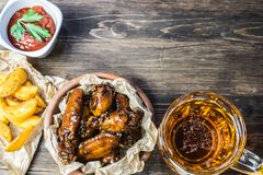 Chicken wings in a fragrant and pungent sauce with sesame seeds. A glass of fresh cold beer and fried potatoes with rustic tomato. Sauce from fresh tomatoes and royalty free stock photography
