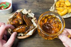 Chicken wings in a fragrant and pungent sauce with sesame seeds. A glass of fresh cold beer and fried potatoes with rustic tomato. Sauce from fresh tomatoes and stock image