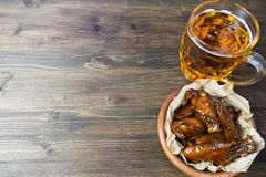 Chicken wings in a fragrant and pungent sauce with sesame seeds. A glass of fresh cold beer and fried potatoes with rustic tomato. Sauce from fresh tomatoes and royalty free stock images