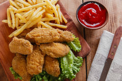 Chicken wings fried in breadcrumbs with sauce and french fries Stock Photo