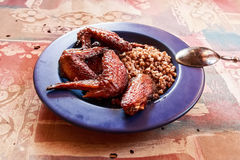 Chicken wings fried with buckwheat on blue plate Stock Images