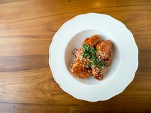 Chicken wings fried. Chicken wing crispy fried with korea sauce on plate with copy space on wood table in restaurant Royalty Free Stock Photo