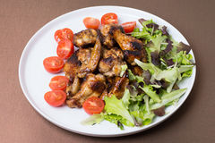 Chicken wings fried with honey decorated tomatoes and leaves. Stock Image