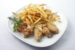 Chicken wings with fried potatoes. Fried chicken wings with french fries on a plate with cherry tomatoes. Raw available stock image