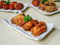 Chicken wings fried. Chicken wing crispy fried with garlic and spicy sauce on plate on wood table in restaurant Royalty Free Stock Photography