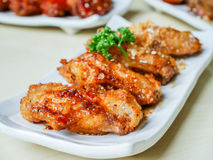 Chicken wings fried. Chicken wing crispy fried with garlic and spicy sauce on plate on wood table in restaurant Royalty Free Stock Image