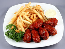 Chicken wings with fries. A view of a white plate filled with barbecue chicken wings, french fries and garnished with sprigs of fresh green parsley stock photography