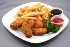 Chicken wings and fries. Plate of chicken wings and fries with condiments on side Royalty Free Stock Images