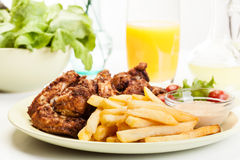 Chicken wings with fries french and spicy sauce Royalty Free Stock Image