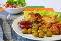 Chicken wings,green olives and vegetable salad. Table setting.Grill wings on lettuce leaves.vegetable salad in a white salad bowl.ketchup in a gravy boat.,green Stock Photography