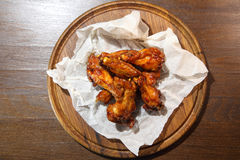Chicken wings in hot sauce, specially prepared for beer. Chicken wings in hot sauce on a wooden plate. Chicken wings in hot sauce, specially prepared for beer Stock Images