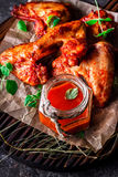 Chicken wings with hot tomato sauce on a chopping board Stock Photography