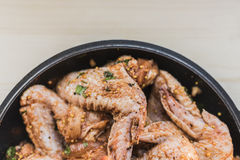 Chicken wings marinated for grilling, at the bottom of the frame. Fresh chicken wings marinated for grilling in spices and grainy mustard in a black frying pan Stock Photo