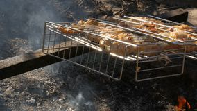 Chicken wings marinated in mayonnaise, seasonings and in onions grilled on fire. Hand overturns the grate stock video