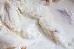 Chicken Wings Marinating. Raw chicken wings marinating in Buttermilk Stock Photos