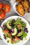 Chicken wings. Plate of fresh salad and chicken wings on wooden table Stock Images