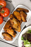 Chicken wings. Plate of chicken wings on wooden table with salad, tomatoes and avocado Royalty Free Stock Image