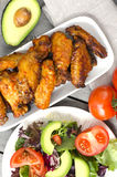 Chicken wings. Plate of  chicken wings on wooden table with salad, tomatoes and avocado Stock Photography