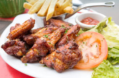 Chicken wings with sauce and golden French fries Royalty Free Stock Image
