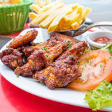 Chicken wings with sauce and golden French fries Stock Images