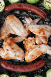 Chicken wings with sausages on grill Royalty Free Stock Image