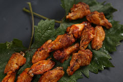 Chicken wings on some leaves. Brown chicken wings on a green vine leaf stock photos