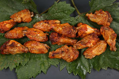 Chicken wings on some leaves. Brown chicken wings on a green vine leaf royalty free stock photo