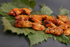 Chicken wings on some leaves. Golden brown chicken wings on a green vine leaf stock images