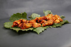 Chicken wings on some leaves. Golden brown chicken wings on a green vine leaf royalty free stock photos