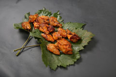 Chicken wings on some leaves. Golden brown chicken wings on a green vine leaf stock image