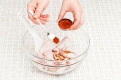 Chicken wings with spices. Cook prepares chicken wings with spices in a glass bowl closeup Royalty Free Stock Photography