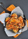 Chicken wings in a sweet and sour sauce with sesame on the pan Royalty Free Stock Image