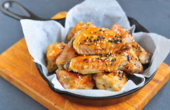 Chicken wings in a sweet and sour sauce with sesame on the pan Royalty Free Stock Photos