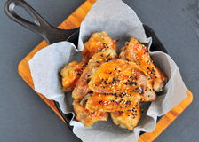 Chicken wings in a sweet and sour sauce with sesame on the pan Stock Photos