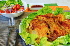 Chicken wings and vegetable salad. Table setting.Grill wings on lettuce leaves.vegetable salad in a white salad bowl.ketchup in a gravy boat Stock Photography