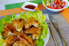 Chicken wings and vegetable salad. Table setting.Grill wings on lettuce leaves.vegetable salad in a white salad bowl.ketchup in a gravy boat Stock Photos