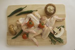 Chicken wings and vegetables on wooden board from above. Closeup of plate with raw chicken wings. copy space for text Royalty Free Stock Images