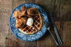 Chicken wings and waffles served with butter and blackberry syrup. On rustic table with negative space Stock Images