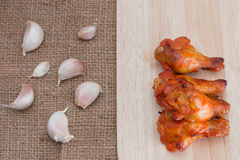 Chicken wings on wooden cutting boards with garlic on brow sack Royalty Free Stock Images