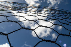 Chicken wire fence. Looking up through a chicken wire fence with a bright cloudy blue sky background stock image