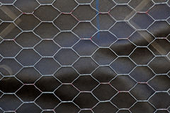 Chicken wire over roofing paper. Section of Chicken wire over black roofing paper royalty free stock photo